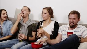 Friendship, communication, party time - cheerful caucasian friends talking, having fun, sitting on couch indoors and. Laughing, eating popcorn, drinking. Male stock video
