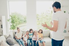 Friendship concept. Now I will tell you the most interesting sto. Ry! Lovely, beautiful kids sit on couch in modern light interior while the father gesticulates royalty free stock photography