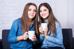 Friendship concept - two beautiful women drinking coffee or tea Stock Images