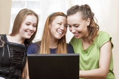 Friendship Concepts: Three Laughing Caucasian Girls Using Laptop Royalty Free Stock Image