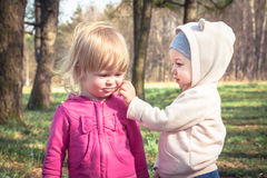 Friendship between cute baby girls playing together in park symbolizing children friendship. Friendship between two cute baby girls playing together in park Stock Image