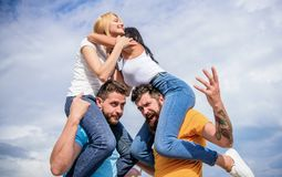 Friendship of families. Couples in love having fun. Men carry girlfriends on shoulders. Summer vacation and fun. Couples. On double date. Inviting another royalty free stock photography
