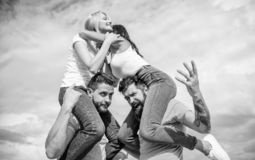 Friendship of families. Couples in love having fun. Men carry girlfriends on shoulders. Summer vacation and fun. Couples. On double date. Inviting another royalty free stock image
