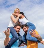Friendship of families. Twice fun on double date. Couples in love having fun. Men carry girlfriends on shoulders. Summer. Vacation and fun. Couples on double royalty free stock image