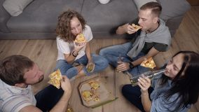 Friendship, food, domestic party time - cheerful caucasian friends order pizza, having fun, sitting on the wooden floor. Indoors and laughing, eating, drinking stock footage