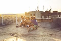Friendship, football and beer. Group of young people sitting on a building rooftop, wearing jerseys, resting after a football match, drinking beer and making a royalty free stock photos