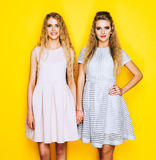 Friendship forever. Two stunning blonde girl in beautiful dresses are friends and stay hands. Royalty Free Stock Photo