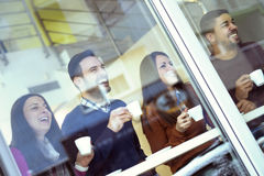Friendship. Friends smiling and sitting in a cafe, drinking coffee and enjoying together.They are having a great time in cafe Royalty Free Stock Photography