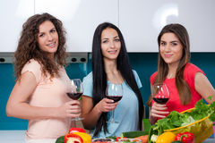 Friendship and good time over a glass of wine. Happy female friends enjoying in the kitchen, spending great time, drinking wine and enjoying while cooking royalty free stock image