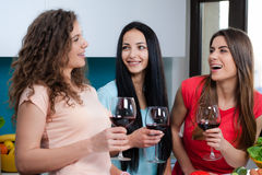 Friendship and good time over a glass of wine. Happy female friends enjoying in the kitchen, spending great time, drinking wine and enjoying while cooking stock images