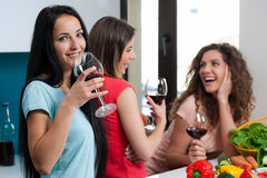 Friendship and good time over a glass of wine. Happy female friends enjoying in the kitchen, spending great time, drinking wine and enjoying while cooking royalty free stock photography