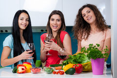 Friendship and good time over a glass of wine. Happy female friends enjoying in the kitchen, spending great time, drinking wine and enjoying while cooking royalty free stock photos