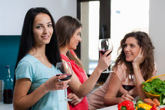 Friendship and good time over a glass of wine. Happy female friends enjoying in the kitchen, spending great time, drinking wine and enjoying while cooking royalty free stock images