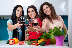 Friendship and good time over a glass of wine. Happy female friends enjoying in the kitchen, spending great time, drinking wine and enjoying while cooking stock photography