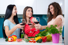 Friendship and good time over a glass of wine. Happy female friends enjoying in the kitchen, spending great time, drinking wine and enjoying while cooking stock image