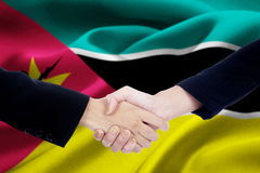 Friendship handshake with flag of Mozambique. Picture of two businesspeople hands in a formal suit, closing a meeting and shaking hands with Mozambique flag Royalty Free Stock Photos