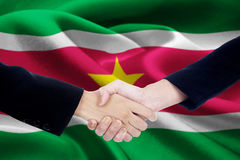 Friendship handshake with flag of Suriname Royalty Free Stock Image