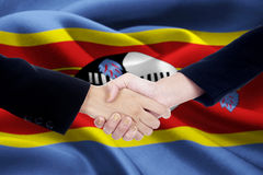 Friendship handshake with flag of Swaziland Royalty Free Stock Photography