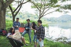 Friendship Hangout Traveling Destination. People Friendship Hangout Traveling Destination Camping Concept near lake Stock Photos