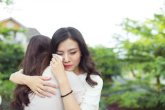 Friendship help support. Depressed asian woman embracing her fri Royalty Free Stock Photo