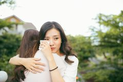 Friendship help support. Depressed asian woman embracing her fri. Friendship help support. Depressed asian women embracing her friend Royalty Free Stock Images