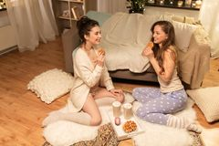 Happy female friends eating waffles at home Stock Images