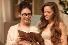 Happy female friends reading book at home Stock Image