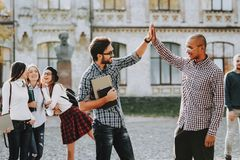 Friendship. Knowledge. Architecture. Two Guys. Greet. High Five. Group of Young People. Courtyard. University. Students. Study Together. Good Mood. Eyeglasses royalty free stock image