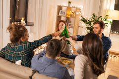 Friends clinking drinks at home in evening stock image