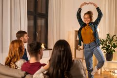 Happy friends playing charades at home in evening stock photography