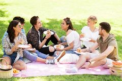 Happy friends eating sandwiches at summer picnic Stock Photos