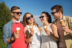 Group of smiling friends with ice cream outdoors. Friendship, leisure and people concept - group of smiling friends with ice cream outdoors in summer stock photos