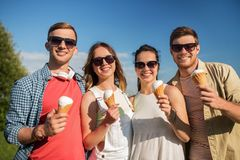 Group of smiling friends with ice cream outdoors. Friendship, leisure and people concept - group of smiling friends with ice cream outdoors in summer stock photo
