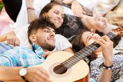 Friends playing guitar and chilling on blanket Stock Photography