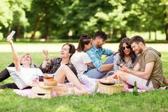 Friends with smartphones on picnic at summer park stock photos