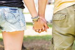 Friendship and love of man and woman - girl and guy hand in hand walking away in nature park - backside of two young guys in love. Royalty Free Stock Images
