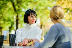 Friendship meeting. Friendship or rivalry. Girls friends drink coffee talk. Conversation of two women cafe terrace. Friendship friendly close relations stock images