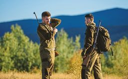 Friendship of men hunters. Military uniform. Army forces. Camouflage. Hunting skills and weapon equipment. How turn. Hunting into hobby. Man hunters with rifle royalty free stock images