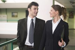 Friendship in the office. Businesswoman and businessman are walking and talking Royalty Free Stock Images