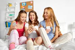 Friends or teen girls with smartphones at home royalty free stock images