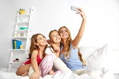 Teenage girls taking selfie by smartphone at home stock images