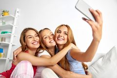 Teenage girls taking selfie by smartphone at home royalty free stock photography