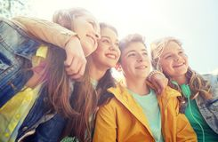 Happy teenage students or friends outdoors stock photography