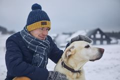 Friendship between pet owner and his dog. Young man stroking labrador retriver in winter landscape stock photo