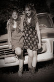 Friendship in Sepia. Two happy pretty teenage BFF girls with long hair, hanging out together in front of an old pickup. Shallow depth of field. Sepia image Royalty Free Stock Photo