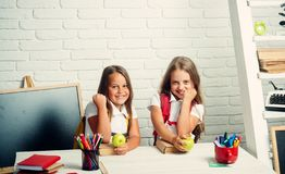 Friendship of small sisters in classroom at knowledge day. Happy school kids at lesson in september 1. Little girls eat. Apple at lunch break. Back to school royalty free stock image