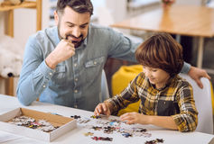 Friendship between son and father while playing. Delighted parent. Happy father wearing jeans shirt keeping his hand on the chic while looking at his playing son Royalty Free Stock Image