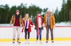 Friends holding hands on outdoor skating rink. Friendship, sport and leisure concept - happy friends holding hands on skating rink over outdoor background Stock Images