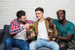 Friendship, sports and entertainment concept. Happy male friends with vuvuzela watching sports on tv. Happy male friends with vuvuzela watching sports on tv royalty free stock images