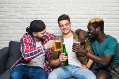 Friendship, sports and entertainment concept. Happy male friends with vuvuzela watching sports on tv. Happy male friends with vuvuzela watching sports on tv royalty free stock photography